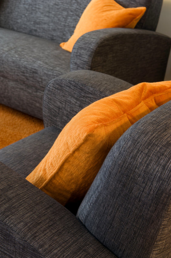 Striking orange pillows on charcoal grey sofa. Sparse pillow use with one pillow in the corner of the sofa.
