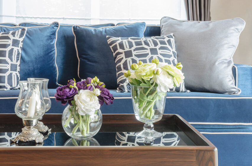 Sofa pillow arrangements for a cool look. Blue and grey pillows on a blue sofa in small pyramid formations.