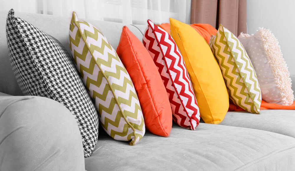 Light grey sofa with overlapping (domino effect) brightly colored throw pillows - brown, orange, red and yellow.