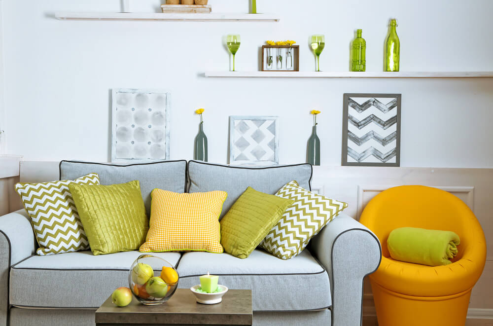 Light blue loveseat with green and yellow pillows in an inverted facing formation.