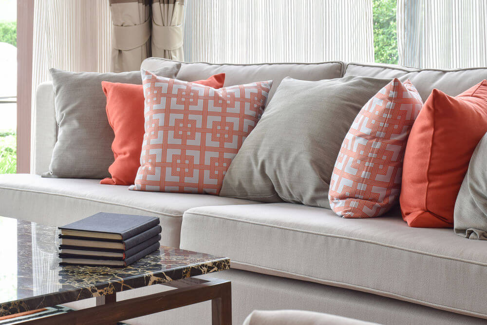 Light grey sofa with a mix of bright orange and matching solid grey throw pillows.