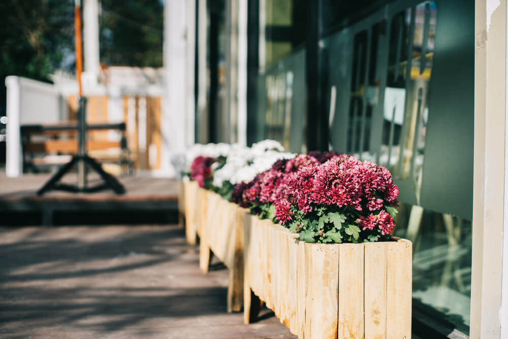 A line of wood planter boxes with flowers lining the edge of a patio.