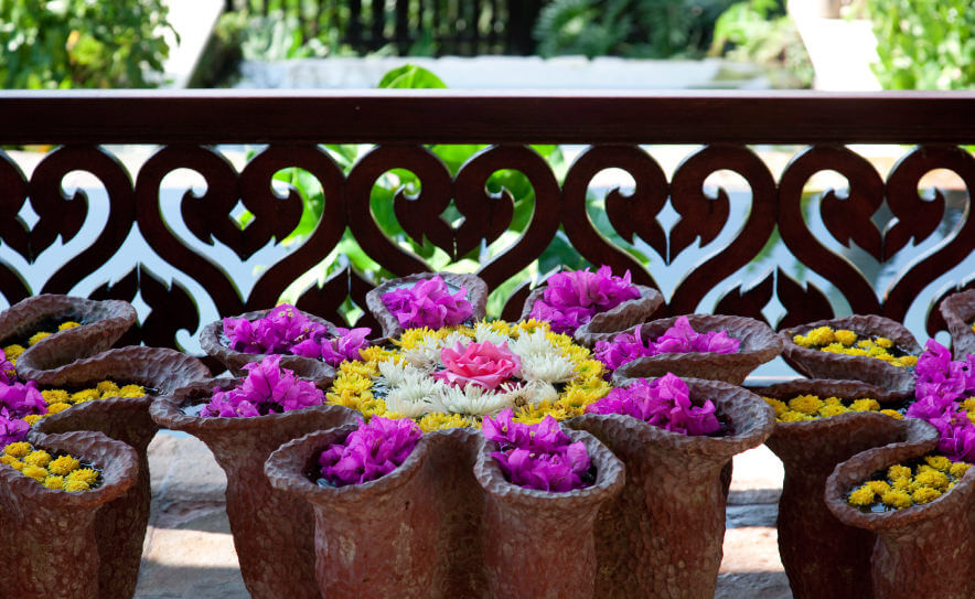 A large cluster of yellow and purple flowers in ceramic pots on a patio with a yellow, white and pink centerpiece.