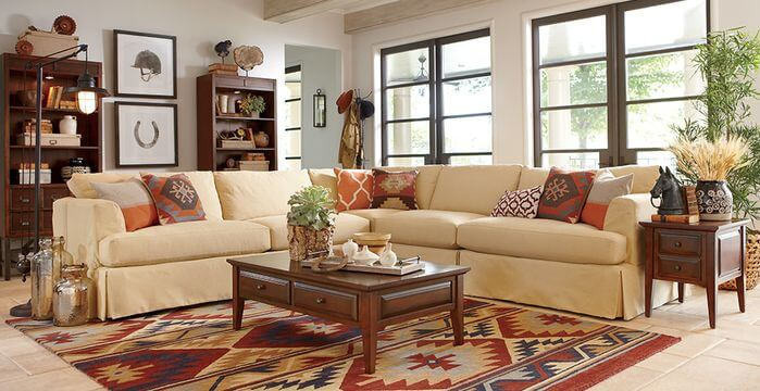 Tan sectional sofa with patterned earth tone throw pillows.