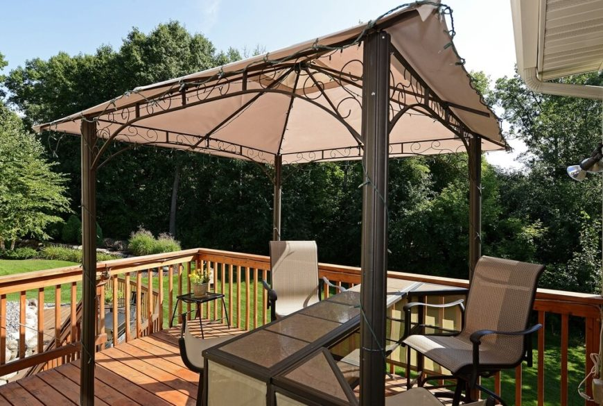 The aluminum swirls at the top of this portable gazebo add style to an otherwise nondescript structure. The owners of this gazebo office area have strung lights around the top of the gazebo.