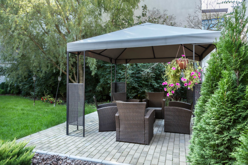 This gazebo is large enough to accommodate five wicker armchairs, shielding any visitors from sun or rain. The mesh panels on each support are a great decorative detail.