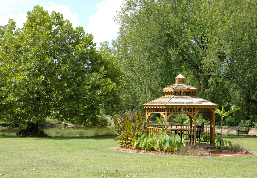 This gazebo sits out in the middle of the yard, with plants and stones surrounding the perimeter. If you want to have a meal away from the house but still desire shade, this gazebo is the ideal spot.