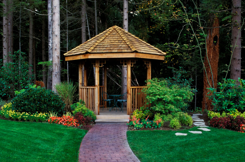This gazebo is surrounded by plants and trees. It sits on this path and acts as a passageway between the manicured lawn and the wilderness of the forest beyond.