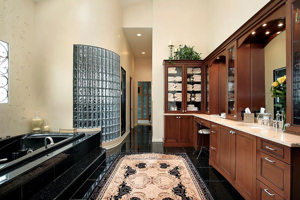 Elegant Primary Bathroom with Black Tile and Rich Wood Van