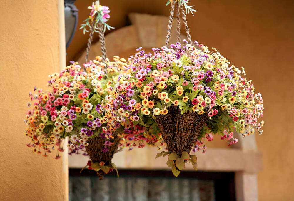 Two unique hanging flower bouquets and triangle organic baskets with large bushy flowers protruding out the top giving it an appearance of two suspended ice cream cones.