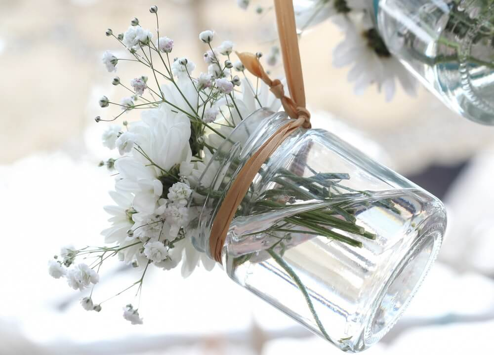 Picture of a clear Mason jar used to a small white flower bouquet. This can be used to decorate an outdoor space by using many of them, for example, around or above a patio space.