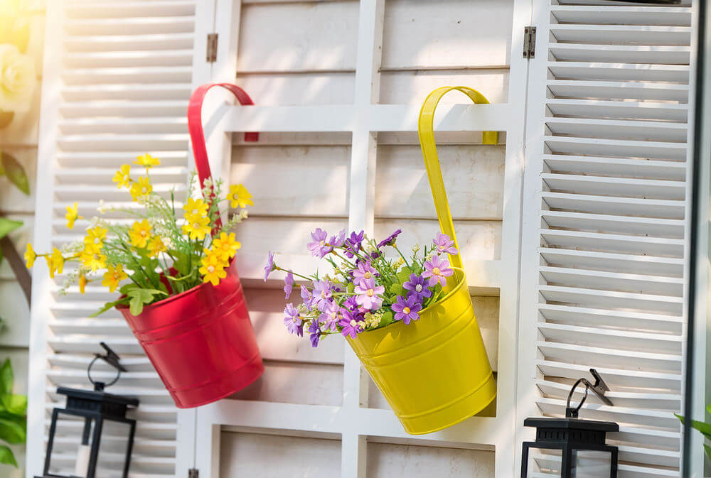 Whimsical metal buckets painted yellow and red with a hanger attached to them hanging from the wall of a house.