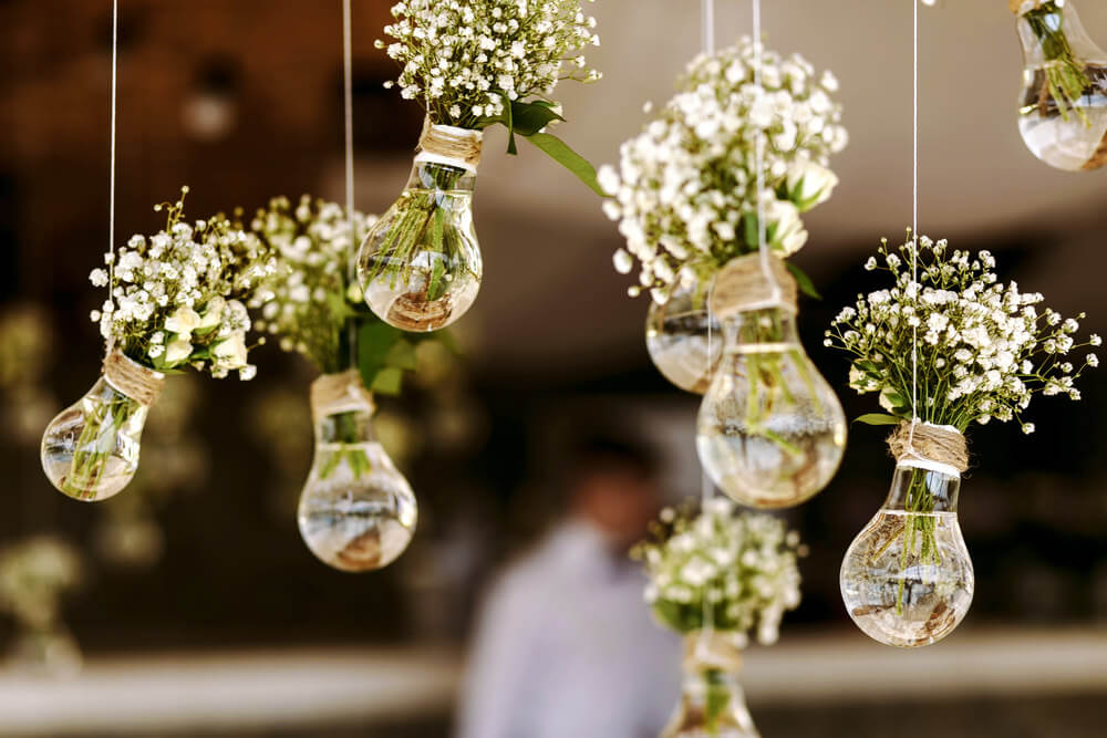 Clear light bulbs used to hold a series of small white flower bouquets.