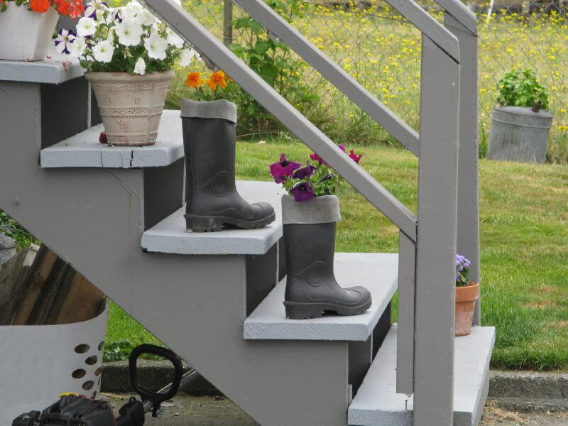 Recycling is one of the easiest and economical way of beautifying your outdoor steps. The grey painted wood steps furnish a nostalgic theme on a nature kissed environment, while the pair of old knee high boots is recycled as flower pots that bring life to colorful petunia blossoms.