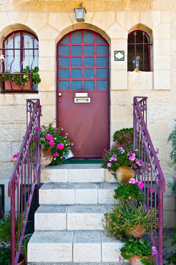 Clay pots planted with flowers gives life to a dull looking staircase and railings. Only one side of the staircase is utilized while two pots are place on both sides of the front door, to prevent from looking overcrowded.