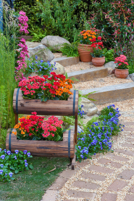These modern and stylish outdoor steps feature bricks, pebbles and huge stones. You can see clay pots in the background but the focus is on the wooden pot stand, where two horizontal wooden pots are fastened. The image shows a mini garden planted with ferns, grass and variety of colorful flowers like baby's breath and pansies.