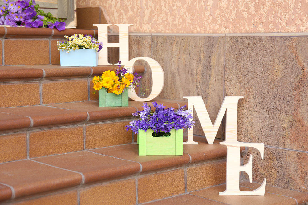 Unpainted yet classic cut wood crafts. This style has fascinated many homeowners. The classic letter cutouts and colored painted wood boxes planted with flowers give the lonely staircase good looking company.