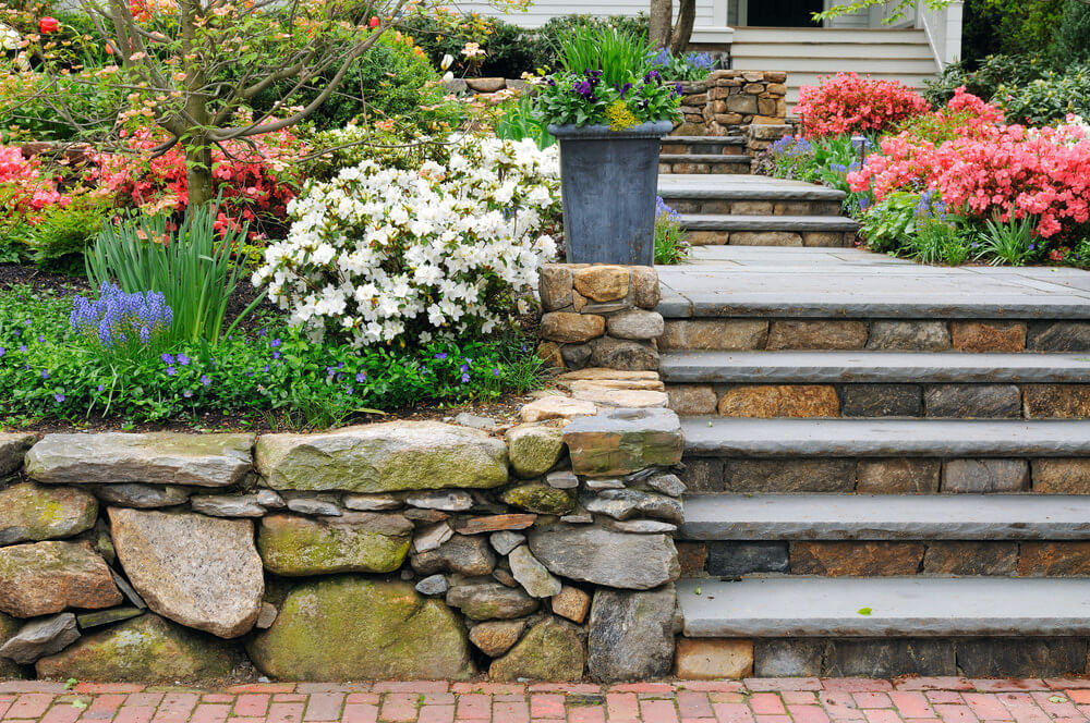 This flower garden is full of colorful perennial flowers and shrubs that line up the neat garden steps, designed in custom made combination of concrete slabs and irregular-sized stones.