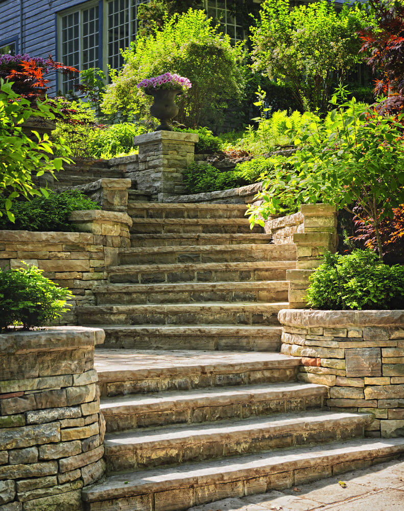A large archaic vase of pink flowers stands in the center of it all as stone-styled planters tuck away green shrubs to make way for the wide garden steps leading to this bend where the pink flowers are the central attraction.