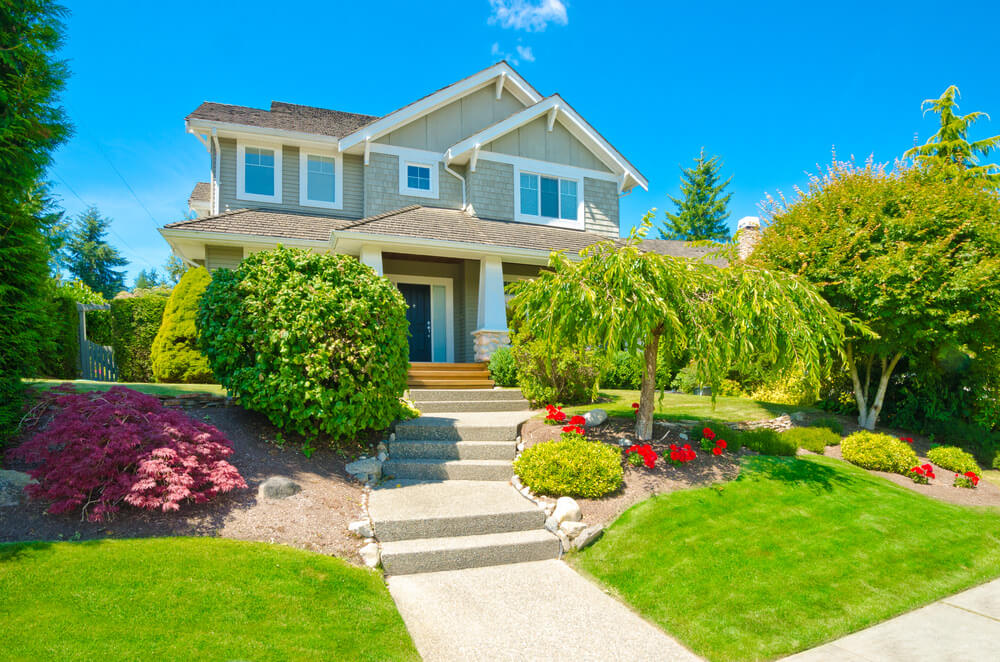 The tidy and cool view of this front yard is featured with greenery and a touch of red blossoms.