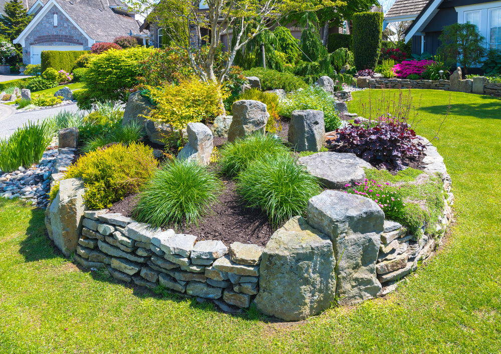 Rubble stones and landscaping grasses delight an otherwise gloomy looking view of this garden.