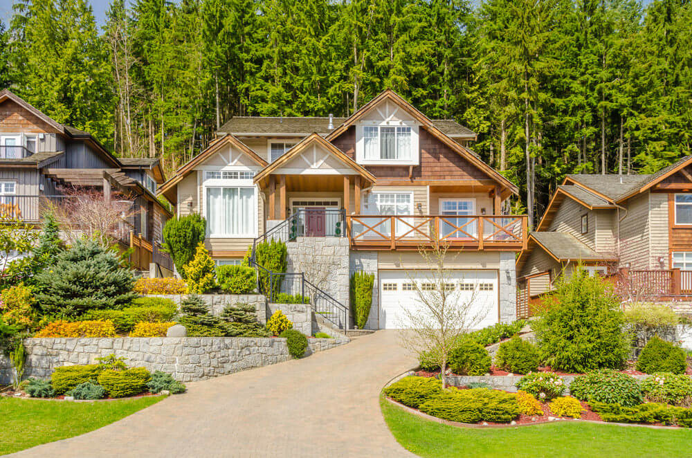 This feels like a breezy pine view. A wooden and brick stone inspired house is furnished with green ornaments along a sloping driveway.