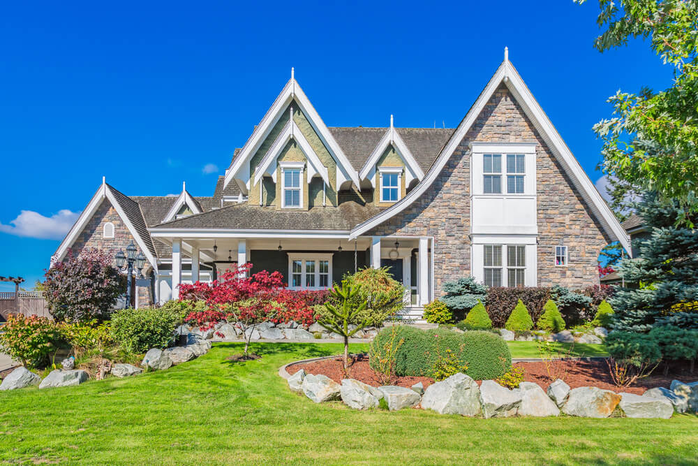 A well-balanced front yard ornamented with medium sized rocks, small trees and trimmed shrubs.