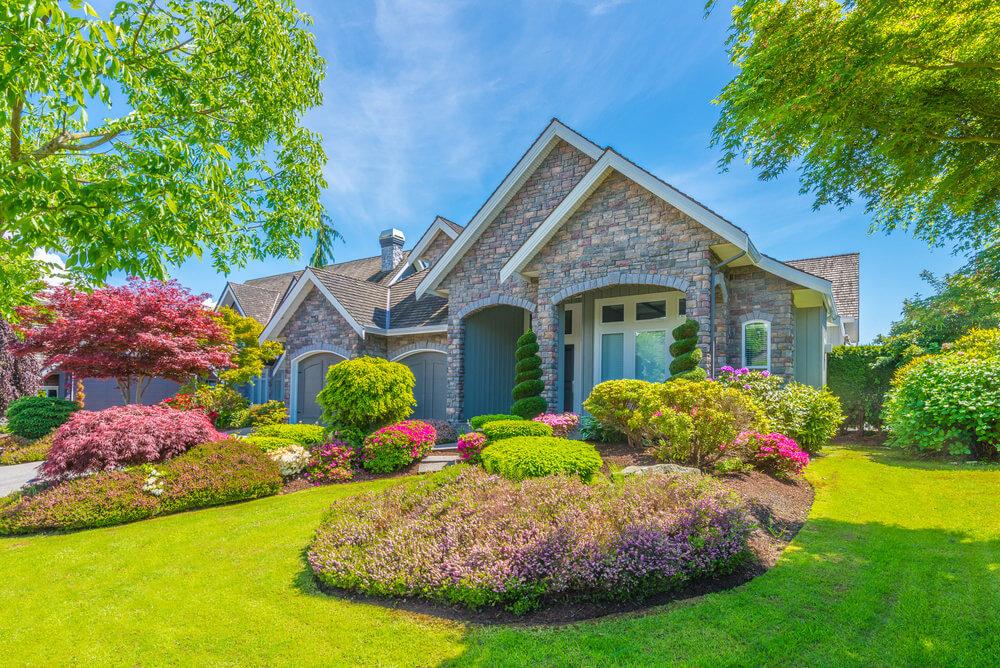 The spiral trimmed topiary standing right in front of the brick stone house has their own spotlight while the purple leaves of nandina and maple tree along with other blossoms gives a touch of colorful sight to the whole landscape.