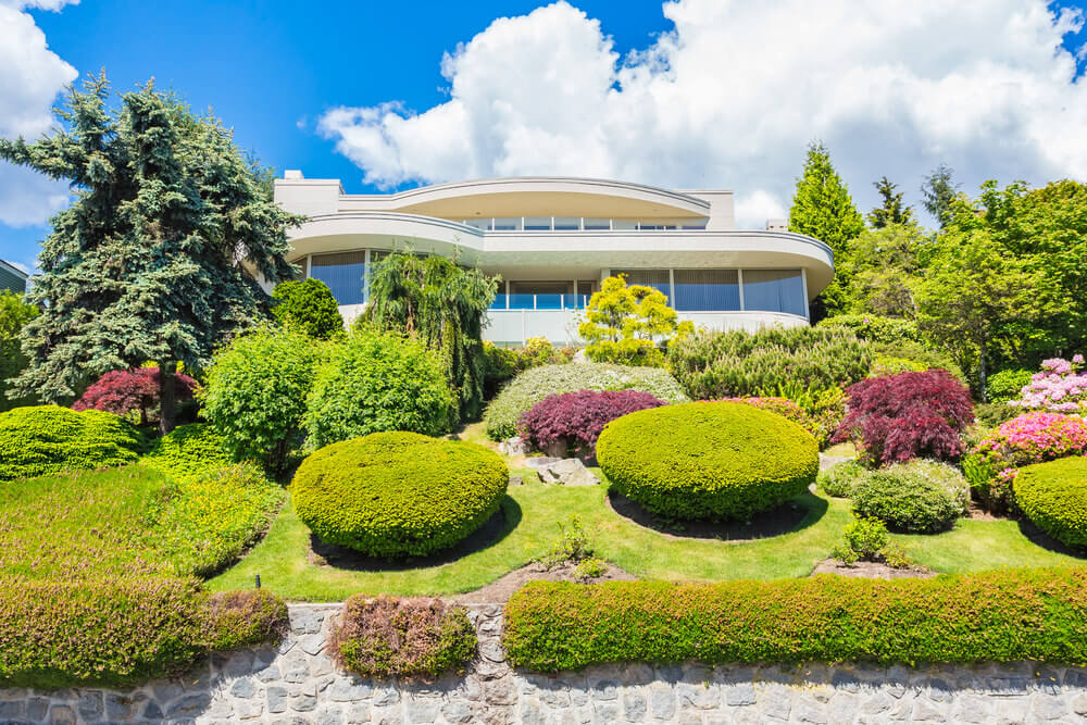 This sloping landscape features large and smaller topiary balls with nandina plants, pine trees and some greenery, perfect for a simply designed vacation house.