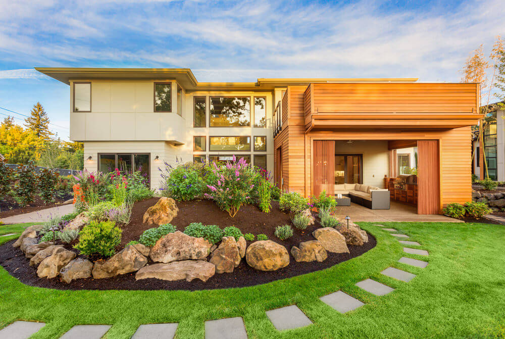 This house is one of modern architecture, designed with a flat rooftop, natural house paint and simple front yard landscape. The landscape is filled with a thick and green turf grass, a pathway encircling it, large stone edging and a few ornamental plants.