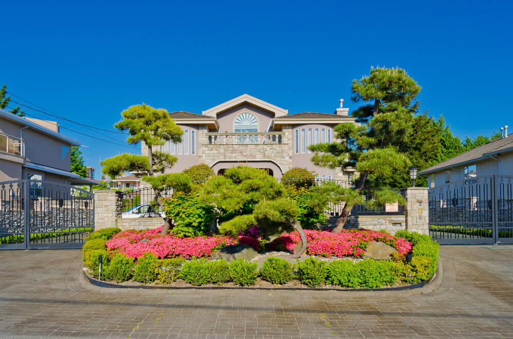 The oval landscape right on the center view of the house is filled with shrubs, pines and blooming red petunias.
