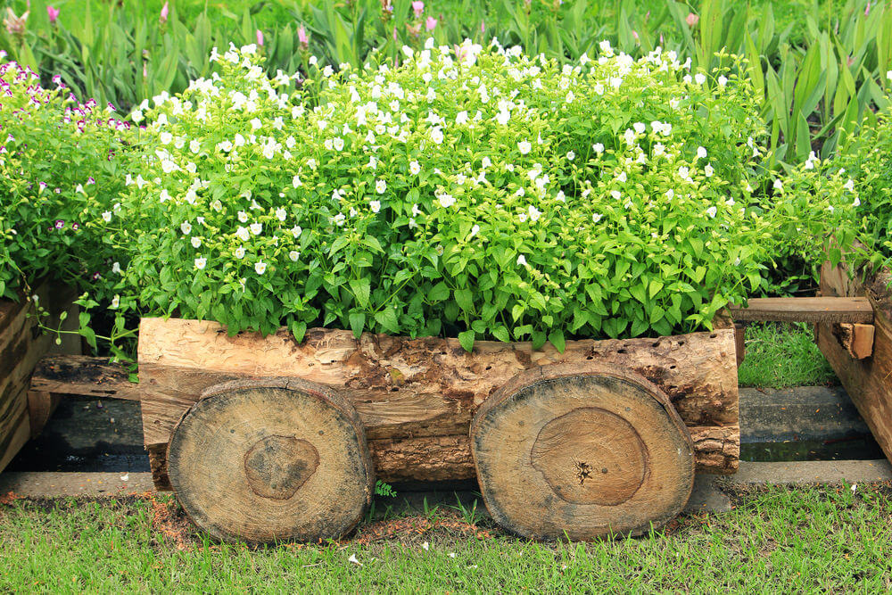 Flower box made to look like a small cart created out of a wood log filled with flowering plants.