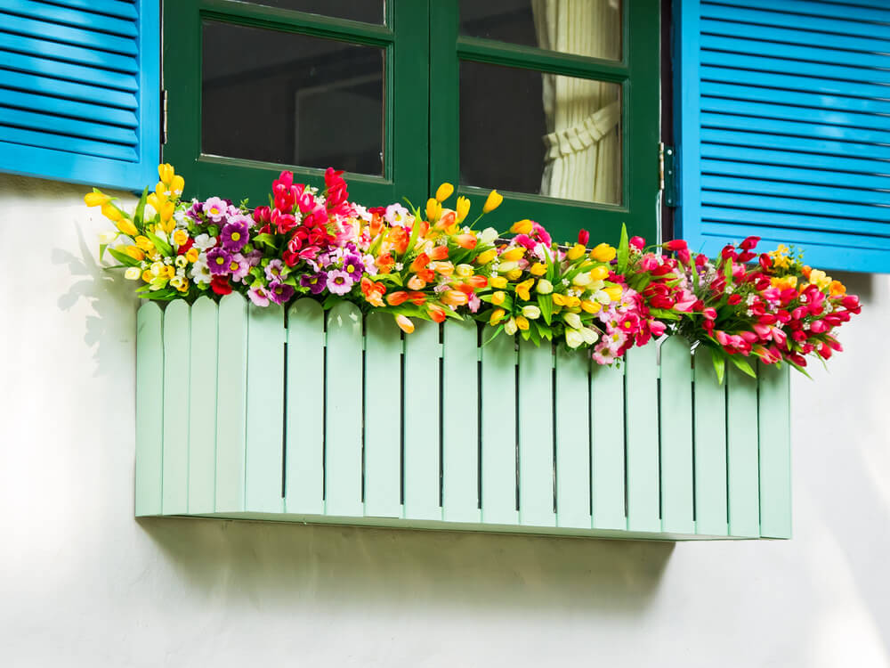 Flower box made to look like a picket fence overflowing with a variety of flowers and colours.