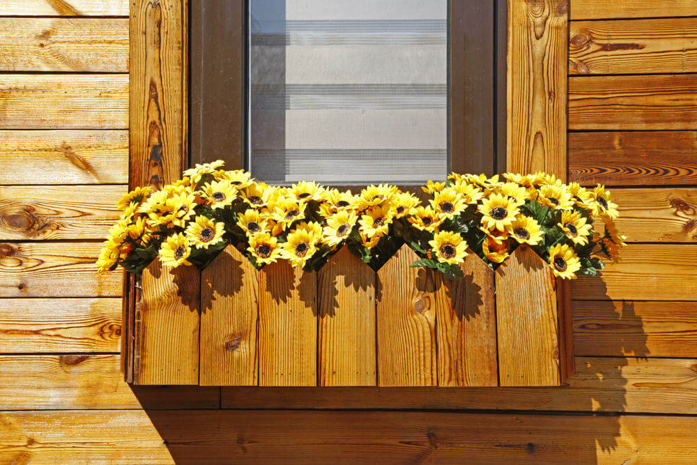 Custom wood flower box created with the same wood of the exterior home placed under a window filled with yellow flowers.