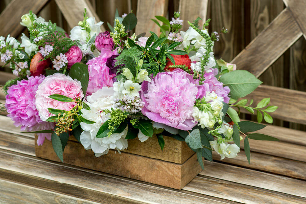 A gorgeous arrangement of pink and white flowers in a nicely crafted wood flower box.