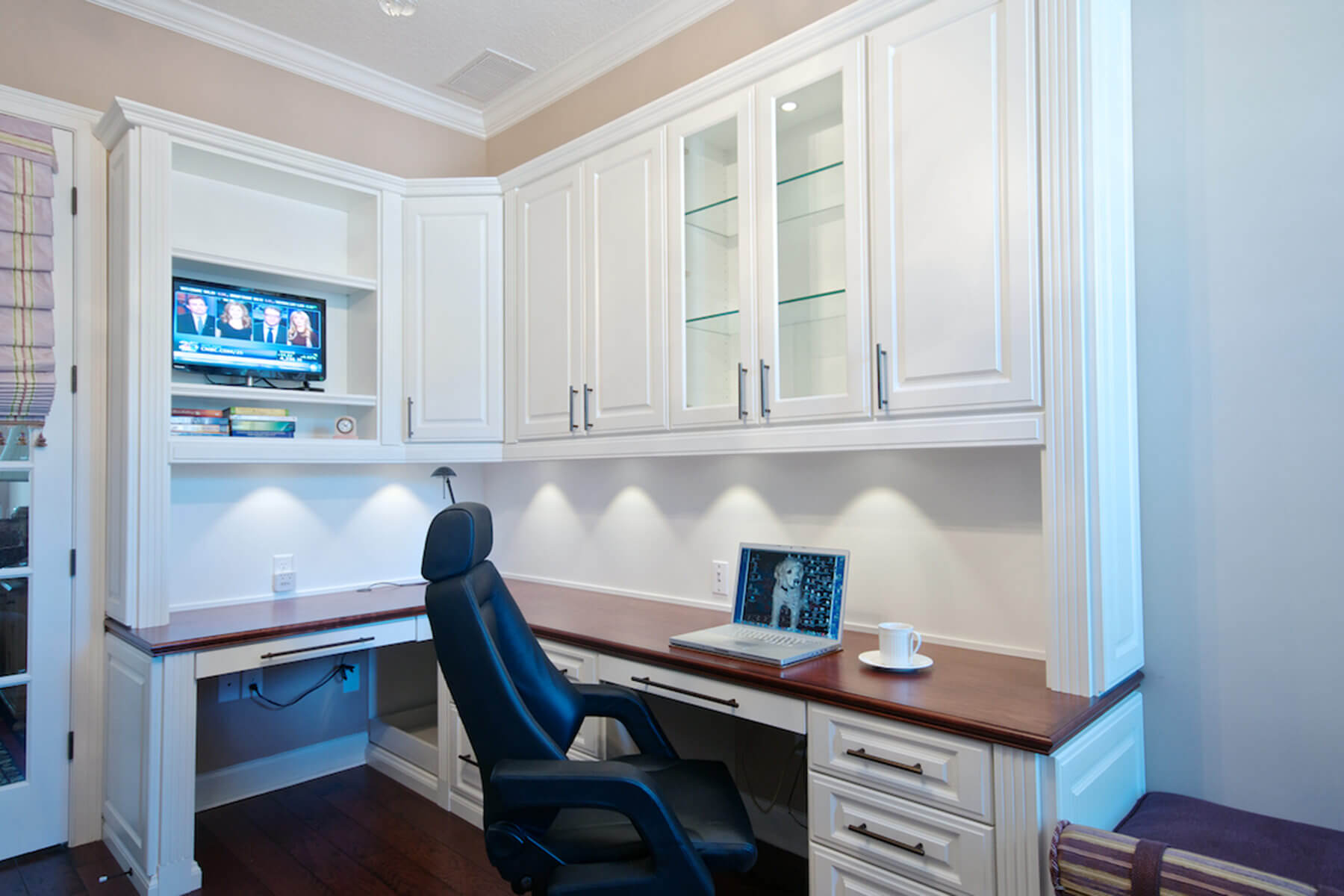 Highly functional l-shaped built-in desk and work station with built-in upper cabinets make this a great small home office that would work for a full time work-from-home space without requiring a large space.