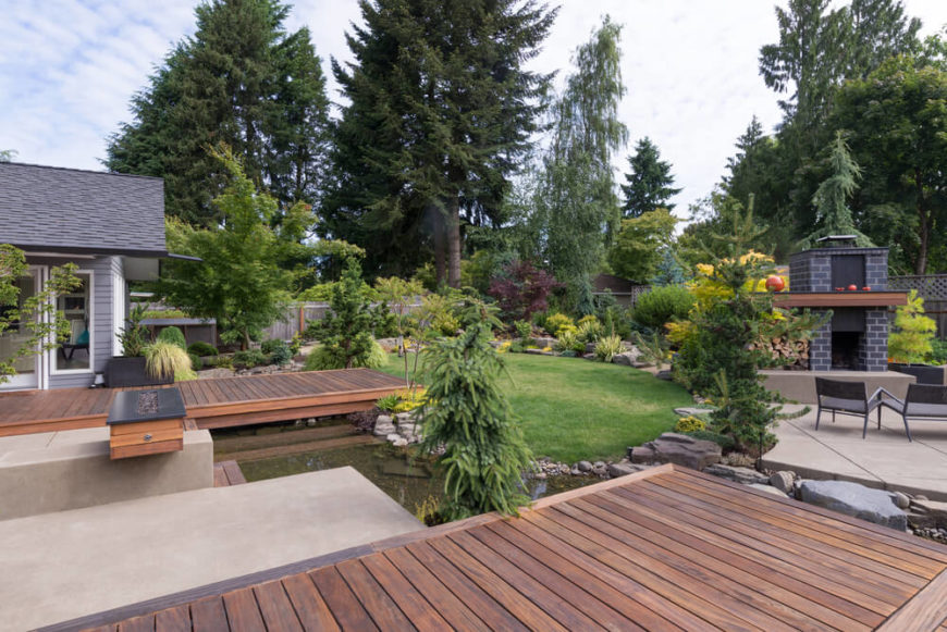 The decks in this yard provide a splash of contemporary style in the landscape, with sharp edges and subtle staining. Both begin near the house and run like a bridge over a small yard pond.