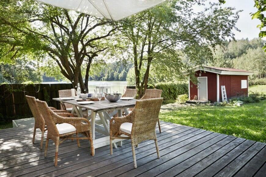Faded, rustic style permeates this floating deck, perfectly in line with the farmhouse style of the home itself. The deck is populated with rich wicker frame chairs and a dining table in the exact same stain.