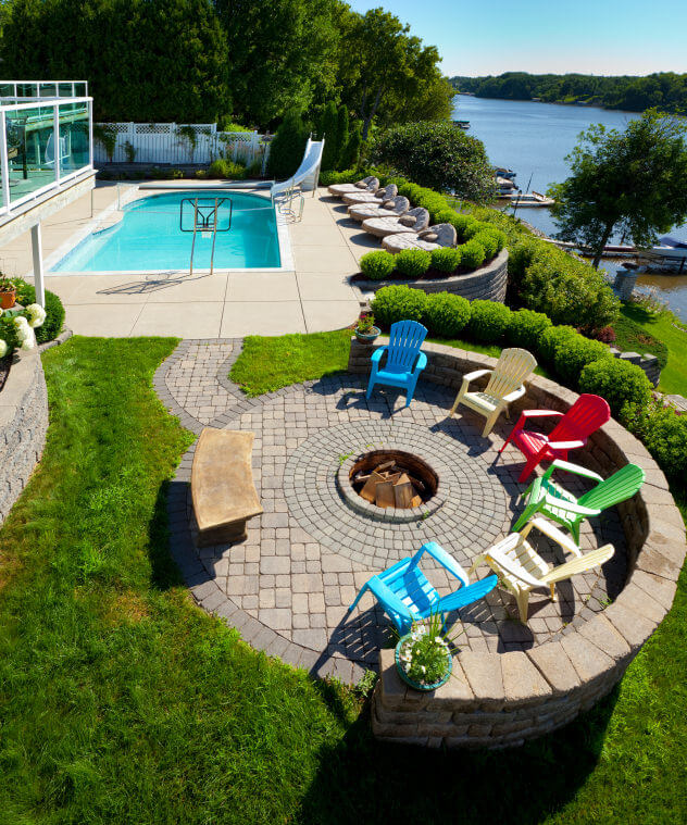 Overhead view of a dog and wood-burning round fire pit in the centre of a brick patio surrounded by colourful Adirondack chairs over looking a pool and a river.