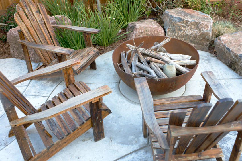 Large metal bowl placed on cement patio serving as a small wood-burning fire pit surrounded by wood Adirondack chairs.