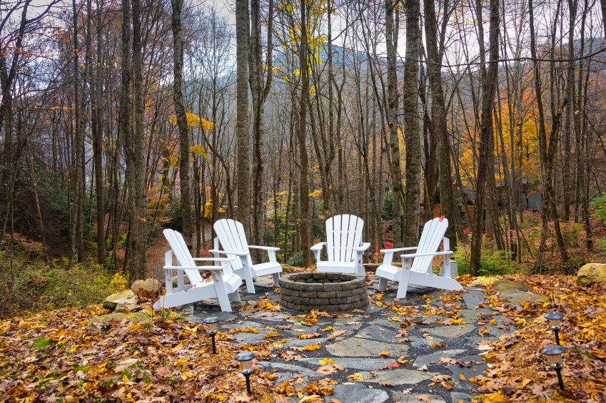 Flagstone Forest patio with brick round fire pit surrounded by striking white Adirondack chairs.