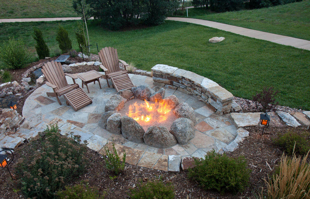 Overhead view of oval flagstone patio with large fire pit created with a series of huge boulders.