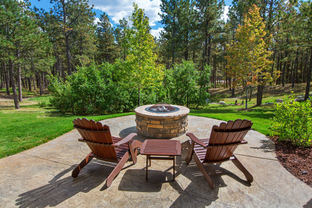 Beautiful patio overlooking the forest and sprawling lawn with a brick round fire pit that has a dome top.
