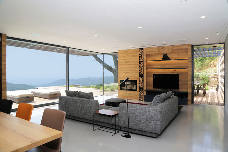 The living room area is centered on a large grey sectional, facing a natural wood feature wall that holds a variety of shelving, the entertainment devices, and a bespoke fireplace.