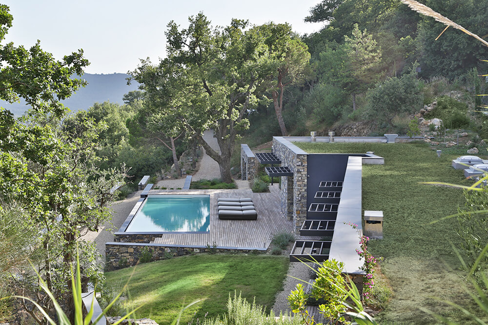 Aerial view of this modern home's pool area surrounded by the home's deck. It also features multiple lounger seats.