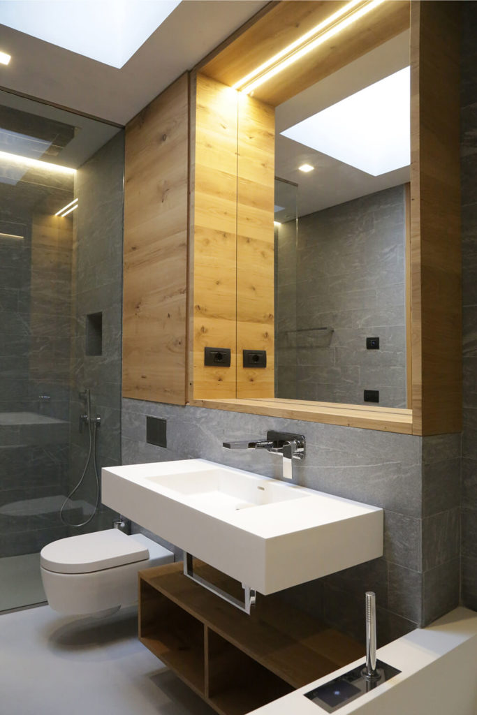 In addition to rich natural wood, the bathroom is wrapped in grey stone bricks and boasts an all-glass walk in shower. The floating vanity is the height of modern design, with a wall mounted faucet.