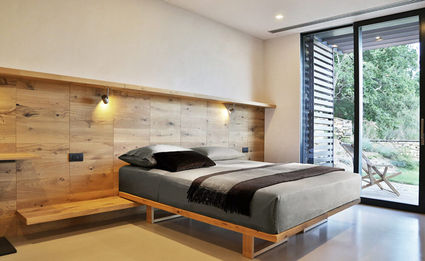 The primary bedroom also holds floor to ceiling glass for a fully integrated indoor-outdoor experience. A rich wood feature wall extends into a shelf that the bed itself rests on.