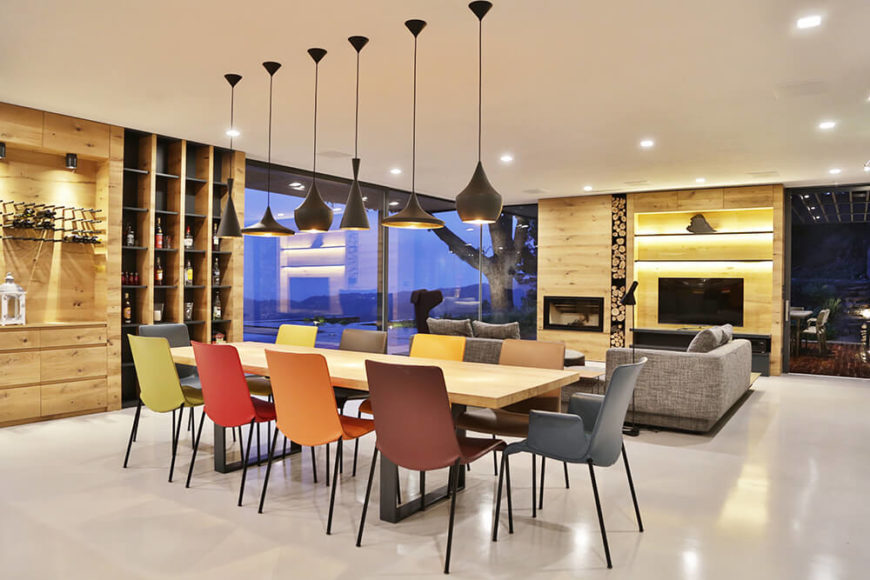 The dining area is defined by a lengthy natural wood table with a black metal frame, surrounded by a muted rainbow of minimalist chairs. Above, a variety of differently shaped pendant lamps hang in charcoal.