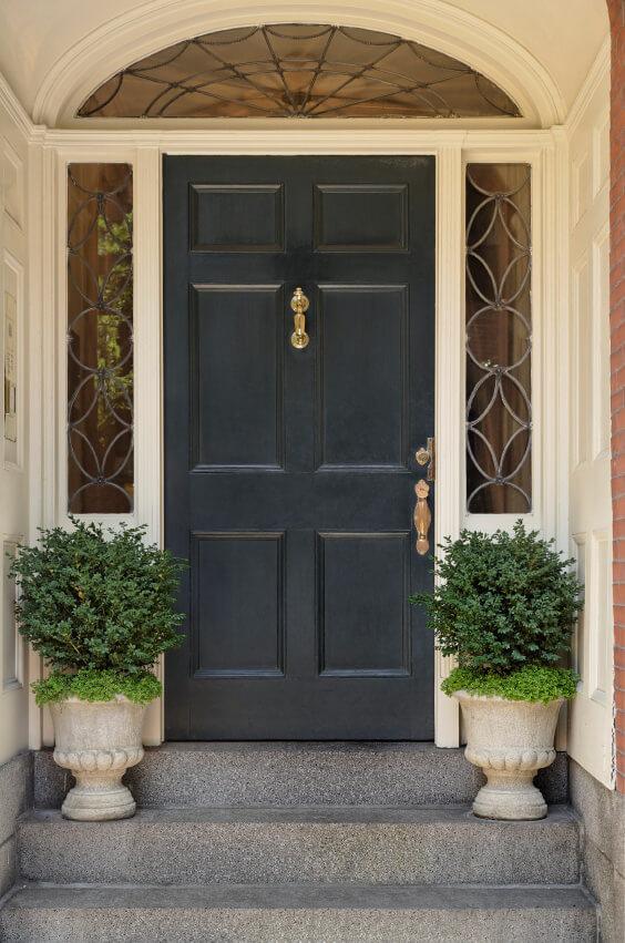 Green shrubs in gothic pots inspire this front door.