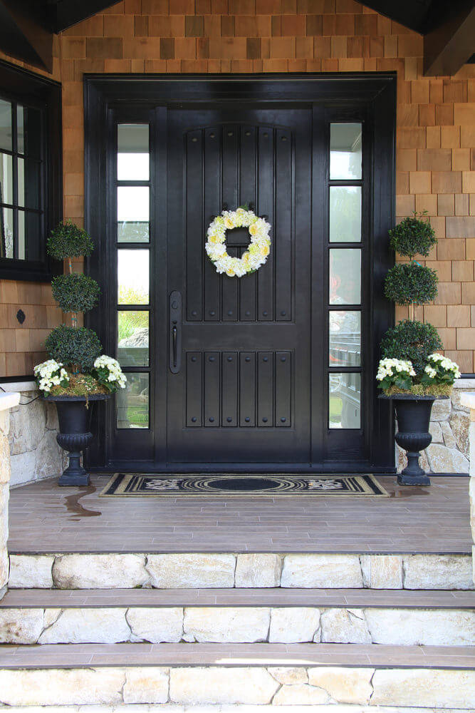 The white floral wreath is the star of this decor while topiary balls highlighted with white flower blossoms in black symmetrical pots stand guard side by side.